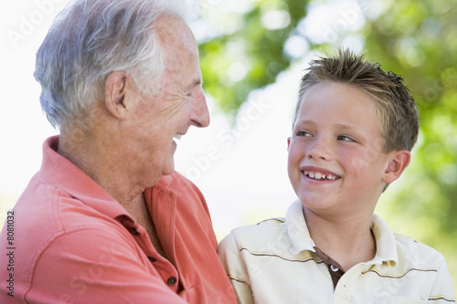 Grandfather and grandson smiling outdoors.