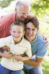 Grandfather with adult son and grandchild in park