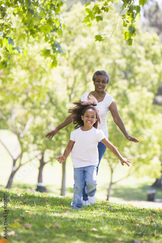Grandmother and granddaughter running in park and smiling