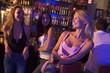 Three young women enjoying drinks together at a nightclub