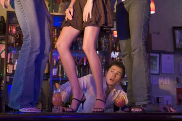 Barman gaping at three young women dancing on bar counter