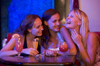 Three young women laughing in a nightclub