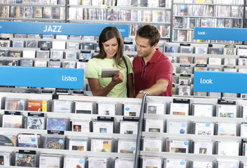 Young couple shopping for jazz CDs in record shop, standing in aisle behind rack, smiling, woman holding CD