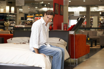 Man sitting at edge of new bed in furniture shop, testing mattress, side view