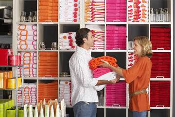 Couple shopping in department store, woman stacking multi-coloured towels in boyfriend's arms, smiling, side view, shelves in background