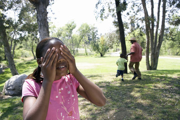 Grandfather playing hide and seek with two grandchildren (5-10) in park, girl covering eyes