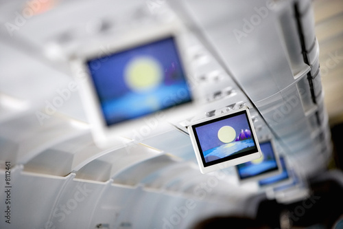 Row of blue visual screens in airplane cabin aisle (differential focus)