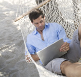 A man using a laptop whilst lying in a hammock