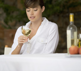 A woman drinking a glass of wine sitting at a table