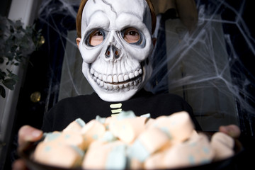 Boy in a skeleton costume at a Hallowe'en party, holding a tray of sweets