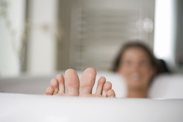 A young woman in the bath, closs-up of feet