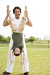 father holding son upside down in the park