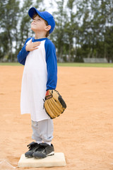 Young boy on baseball base praying
