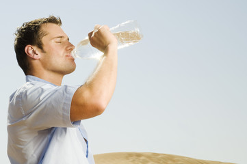 A man in a desert drinking from a bottle of water