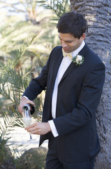 A groom pouring a glass of champagne