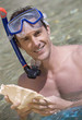 A male snorkeler holding a shell