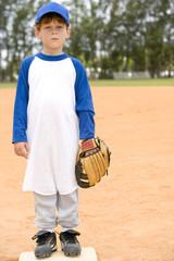 Portrait young boy on baseball base
