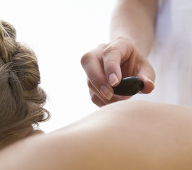 A young woman receiving a hot stone holistic treatment