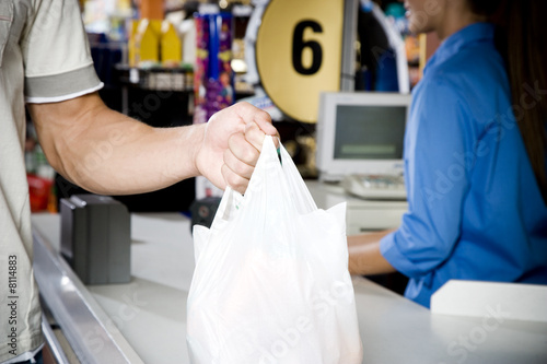 Close up of customer and supermarket checkout assistant