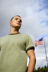 A young man standing by an American flag
