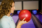 Woman in a bowling alley, holding a red bowling ball