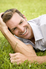 portrait man lying on grass leaning on elbow