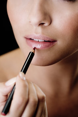 Woman using a lip pencil