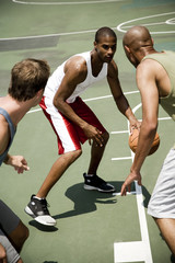 Three men playing basketball on an outdoor court