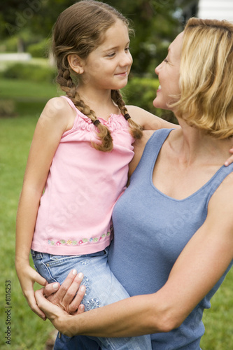 mother carrying daughter in garden