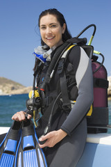 A female scuba diver sitting on a boat