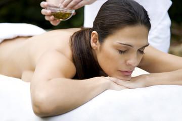 Hispanic woman receiving a massage in a tropical setting