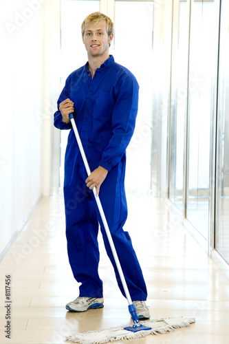 Janitor or cleaning man sweeping the floor of a modern office
