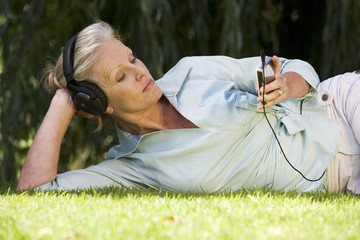 A senior woman listening to music