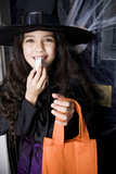 Girl in a witch's costume at a Hallowe'en parting, eating sweets
