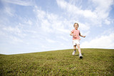 A young girl running across a hill