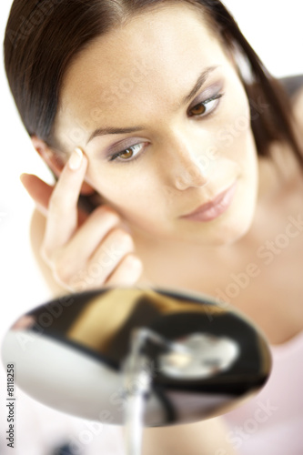 Young woman checking make-up, close-up