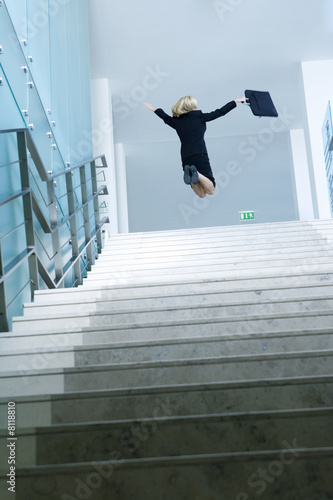 A businesswoman jumping at the top of stairs