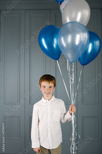 boy holding a bunch of balloons
