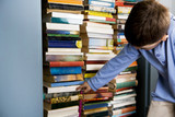 little boy looking for book in bookshelf
