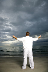 A man standing on a stormy beach
