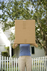 Woman moving house, carrying large packing box
