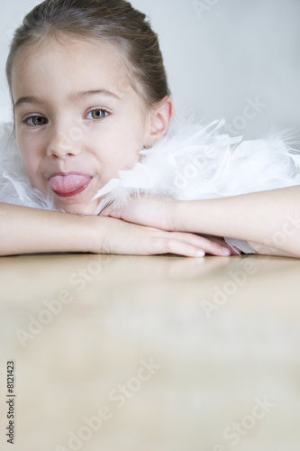 Portrait of a young girl with a feather boa in dressing up clothes poking her tongue out
