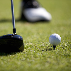 Close-up of a golf club and ball on a tee