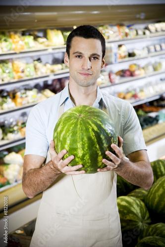 Portrait of a supermarket shop assistant holding a watermelon