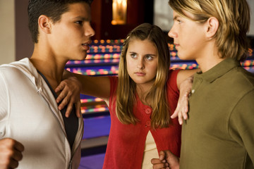 Argument between teenage boys in a bowling alley, girl mediating between them