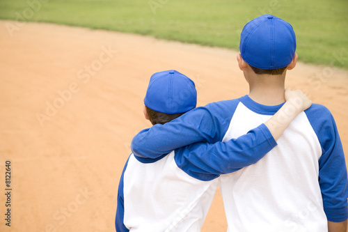 two boys walking away with arms around each other's shoulders