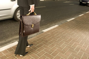 A businesswoman walking on a pavement