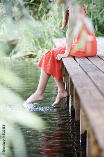 Young woman sitting by a river