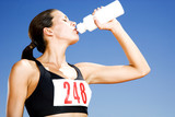 Portrait of a female athlete drinking form a water bottle