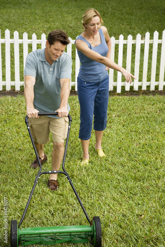 man mowing the lawn, wife pointing at grass